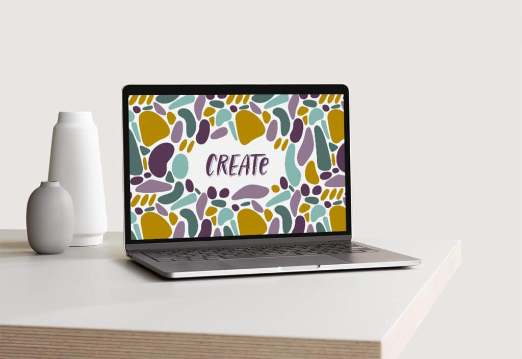 Laptop with an abstract graphic with handlettered word CREATE